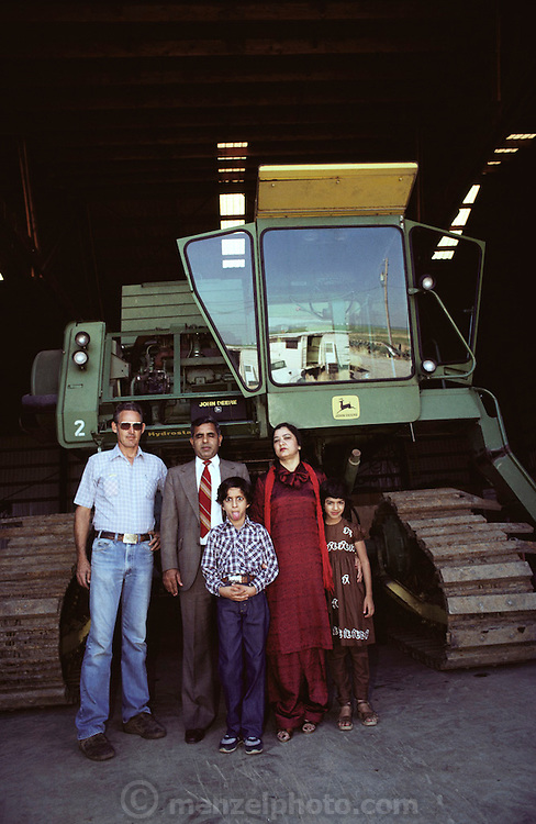 Butte City, California. Hussain family by his John Deere tracked tractor. Mr. Hussain, a rice farmer, is blind. He is accompanied by his farm manager, his wife and son and daughter. MODEL RELEASED.