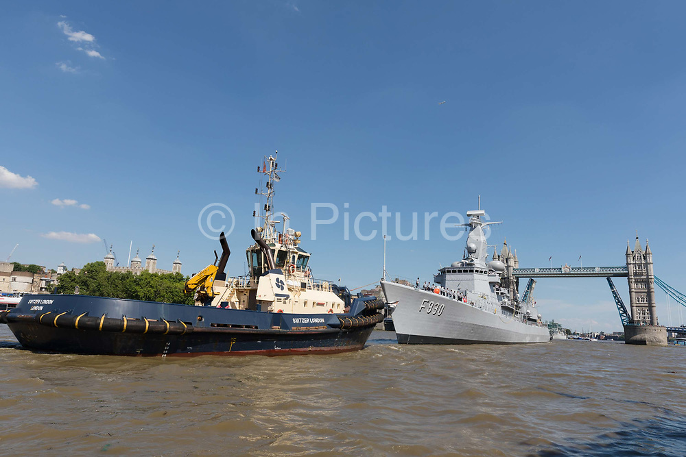 The Belgian Frigate Leopold I F930 of the Belgian Navy leaving London with assistance from tugs under Tower Bridge on the River Thames following a London visit on July 15, 2018 in London, England. Leopold I F930 is a Karel Doorman-class frigate and is 122m 401.33 ft long with a displacement of 2,800 tonnes and has taken part in anti-drug operations in the Caribbean together with the US Navy, was part of the UN operations in the Adriatic Sea during the conflicts in the former republics of Yugoslavia, as well as various NATO exercises.