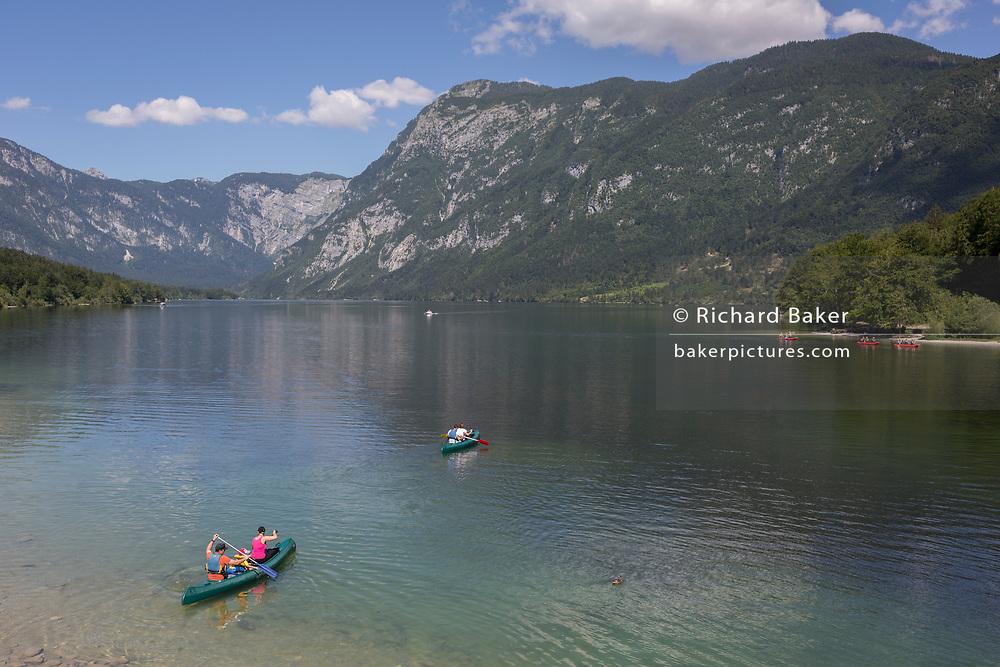 Canoes head out into lake Bohinj from at Ribcev Laz, on 19th June, in Lake Bohinj, Sovenia