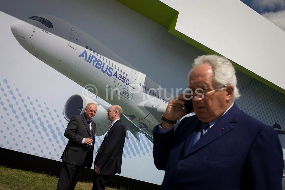 Visitors beneath a large billboard of the Airbus A350 XWB on the side of the Airbus corporate chalet at the Farnborough Air Show, England. The A350 XWB is the only all-new aircraft in the 300-400 seat category. The A350 XWB is a family of long-range, two-engined wide-body jet airliners developed by European aircraft manufacturer Airbus. The A350 is the first Airbus with both fuselage and wing structures made primarily of carbon-fiber-reinforced polymer. It's scheduled to enter commercial service later in 2014.