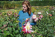 Jenn owner of 'Blooming Green Flowers', Kent, picking flowers in her farm<br /><br />Jen is the owner at 'Blooming Green Flowers'. She runs the farm with her partner Bek. Blooming Green Flowers is a British flower farm is near Marden Kent, south of Maidstone, not far from London. Wedding parties come to collect their flowers, typically on a Thursday, Friday or Saturday morning. In the summer, on Friday afternoons families, everyone, from the very young to old come to pick flowers. Cost £10 a container.<br /><br />British local flowers, grown nearby, count for around 10% of the UK market, traveling less than a tenth of their foreign counterparts which are often flown in from abroad. Nearly 90% of the flowers sold in the UK are actually imported, and many travel over 3000 miles. Local flower farms help biodiversity, providing food and habitat to a huge variety of wildlife, insects including butterflies, bugs, and bees. Often local flower farmers prefer to grow organic rather than using pesticides. British flowers bloom all the year around, even in the depths of winter, and there are local flower farms throughout the country.<br /><br />Many people like the idea of the just picked from the garden look, and come to flower farms throughout Britain to pick their own for weddings, parties and garden fetes. Others come for the joy of a day out in the countryside with their family. Often a bride and her family will come to pick the flowers for her own wedding, some even plant the seeds earlier in the year.