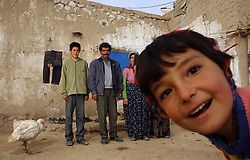 Ali Ipak and his wife Ayse gather with neighbors in front of their home as turkeys that were given to them by the Food and Agricultural Organization telefood project run around December 13, 2005 in central Turkey, Konya in Kutoren district, about 400 kilometers from Ankara. The projects are meant to improve rural poor families livelihoods. (Ami Vitale)