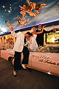 An Elvis impersonator and a newly wed couple in a Cadillac Convertible at an Elvis Themed Wedding in Las Vegas, Nevada, USA. June 2004. The ceremony took place at A Little White Wedding Chapel. The wedding industry is the third largest in Las Vegas after gambling and entertainment.