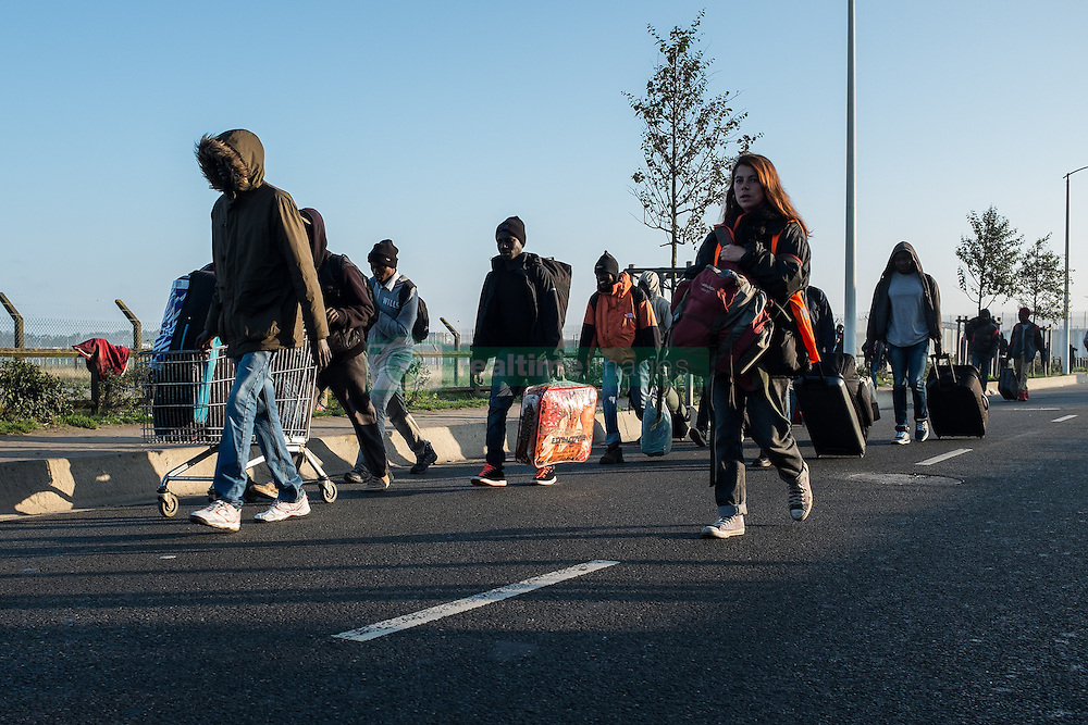 October 25, 2016 - Calais, France - Migrants are walking in the Calais Jungle with their luggage towards the registration center  in Calais, France, on 25 October 2016. Up to the evening, about 4,000 migrants from the Refugee camp on the coast at the English Channel were distributed to several regions in France. The police have begun to tear down the huts and tents in the camp. (Credit Image: © Markus Heine/NurPhoto via ZUMA Press)