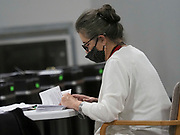 An election worker counts the number of mail-in absentee ballots she opened before bundling them up for the next step in ballot processing.