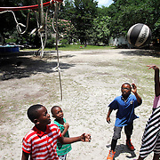 """Trevionne Blue, 9, from left, Lagarrick Donaldson, 5, Tayshaun Donaldson, 7, and Zyasia Aiken, 7, play a ball game of """"21""""on Thursday afternoon in a grass lot near their homes north of the Marine Corps Air Station Beaufort off of Bruce K. Smalls Drive."""