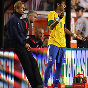 Neymar, Brazil, (right) is watched by USA coach Jurgen Klinsmann during the USA V Brazil International friendly soccer match at FedEx Field, Washington DC, USA. 30th May 2012. Photo Tim Clayton
