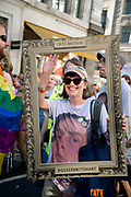 Pride in London, formally known as Pride London, is an annual LGBT pride festival and parade held each summer in London, United Kingdom. A woman who is part of a group from Tate holds a picture frame saying Queer British Art in front of herself wearing a t shirt from the current Queer Art exhibition.