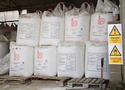 Danger fertiliser store oxidising agent sign Ammonia Nitrate bags in barn, Suffolk, England
