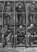 Prisoners at Clerkenwell House of Correction, London,  taking their turn on the treadmill while the men who have just done their stint wait in silence until it is their turn again.  From 'The Illustrated London News', 4 July 1874. Wood engraving