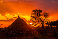 Silhouette of huts at sunset, a Hamer tribe village, near Turmi, Omo Valley, Southern Nations Nationalities and People's Region, Ethiopia