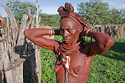 A Himba tribeswoman fixes her hair outside her home in the small village of Okapembambu in northwestern Namibia, during the rainy season in March. The Himba diet consists of corn meal porridge and sour cow's milk.  Like most traditional Himba women, she covers herself from head to toe with an ochre powder, cow butter blend.