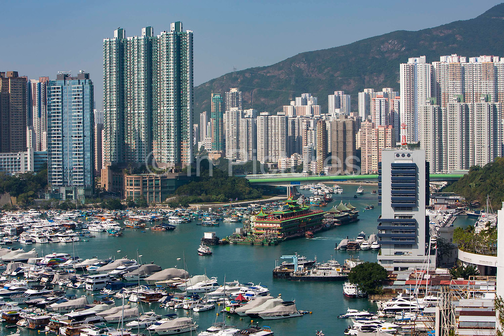 A view of the Hong Kong skyline overlooking boats in Aberdeen Bay during the day in Hong Kong. The large boat on the right holds the Jumbo Floating restaurants.