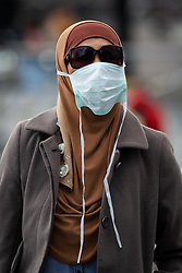 © Licensed to London News Pictures. 14/03/2020. London, UK. A woman tourist wearing a hijab and medical mask walks near Tower Bridge in London this afternoon. The coronavirus is continuing to spread across Europe and the UK and today Spain is reportedly in lockdown for all non essential travel. Photo credit: Vickie Flores/LNP