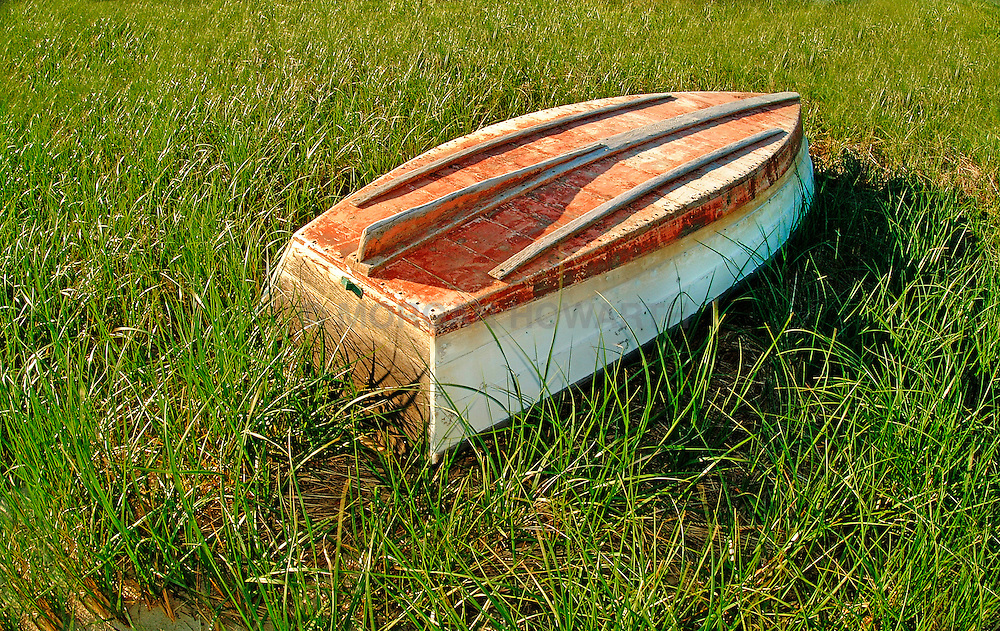 Old row boat turned over on grass