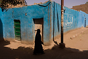 A local woman walks past a blue painted wall in a village near Medinet Habu on the West Bank of Luxor, Nile Valley, Egypt. This scene is typical of the quiet pace of rural everyday life, far away from the chaotic capital, Cairo whose government controls the policies that affect the people of small villages.