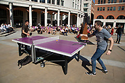 Two men playing outdoor table tennis in the sunshine in Paternoster Square in the City of London, England, United Kingdom.