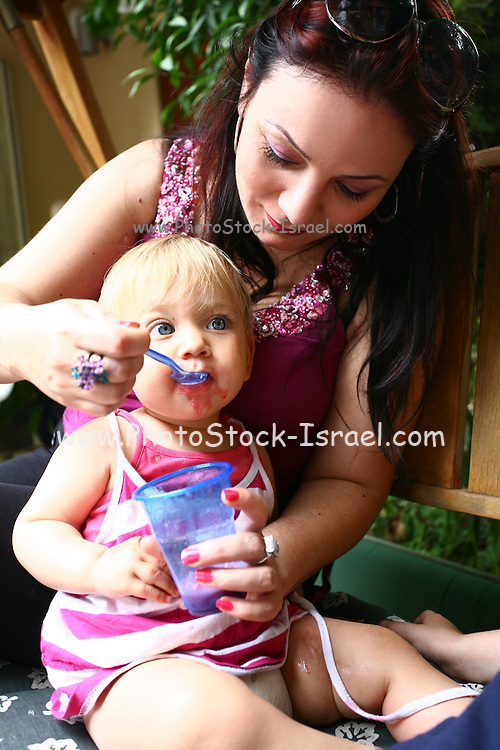 Young Mother feeds her baby aged one year Model Release available