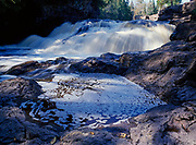 Natural foam floating on rock pool below Fifth Falls, Gooseberry River, Gooseberry Falls State Park, Minnesota.