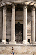A woman walks beneath the pillars and column architecture of Sir Christopher Wrens St Pauls Cathedral south transept, on 24th June 2021, in London, England.