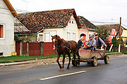 Romania, Transylvania, Biertan, village street family ride in a cart pulled by a horse