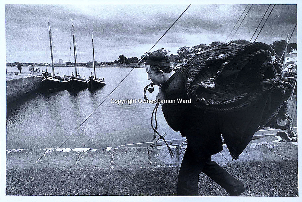 Paddy Dundass carries ashore the Sails from Chapall, the Oldest boat taking part in the Crinniu na mbad (Gathering of the Boats ) at Kinvara ,Co Galway,Ireland in 1993...Photograph by Eamon Ward
