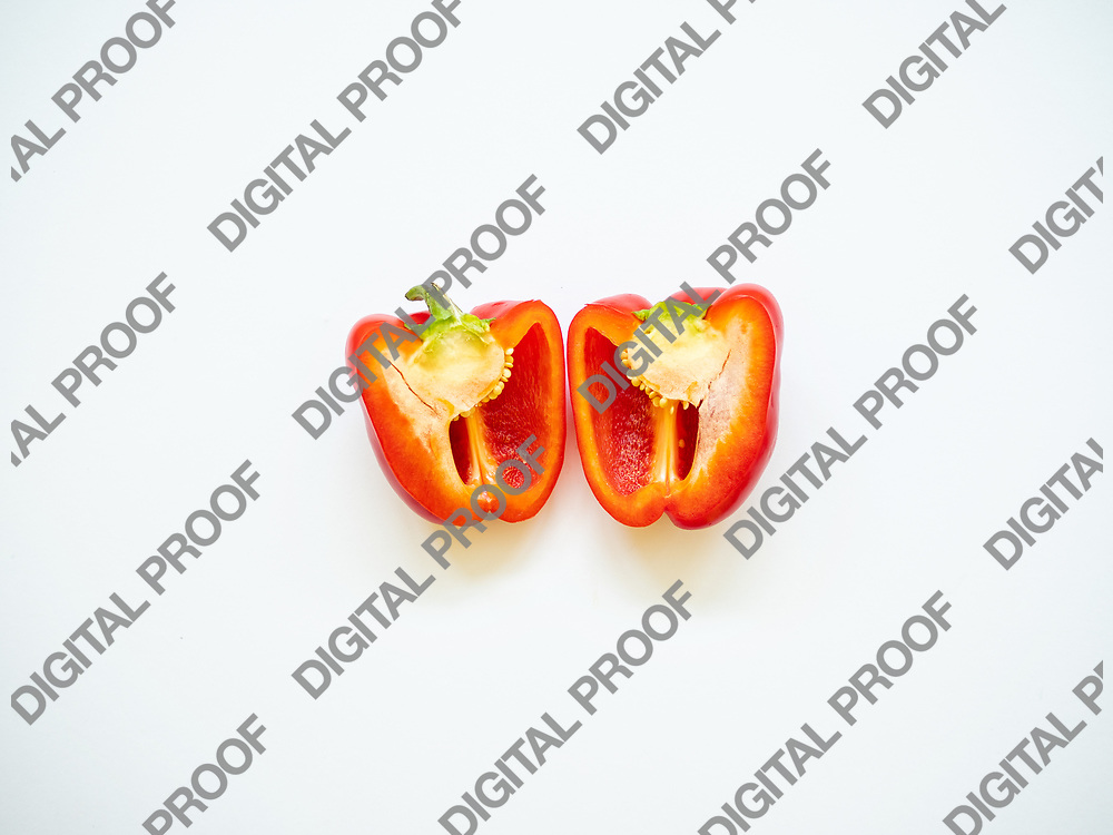 Red bell pepper sliced with seeds isolated in white background viewed from above - flatlay look