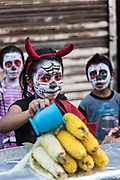 A young Mexican girl wearing face paint smiles as she sells roasted corn outside the town cemetery during the Day of the Dead festival November 2, 2017 in Quiroga, Michoacan, Mexico.  The festival has been celebrated since the Aztec empire celebrates ancestors and deceased loved ones.