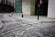Incongruous modern corporate architecture and older cycling road markings. The empty landscape in the City of London suggests a vacant metropolis devoid of the working population who are at home, leaving the streets emptied of commuters and pedestrians. The road junction is old, even ancient as the City of London was founded in AD43 and centuries of development (despite the Great Fire in 1666) has kept to the ancient boundaries. The Square Mile, as the City is also known, has a resident population of under 10,000 but a daily working population of 311,000.