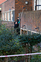 A police officer uses a mirror on a telescopic handle to search for evidence on a housing estate behind where a 17 year-old boy died after being stabbed on Caledonian Road, Islington, North London. London, January 30 2019.
