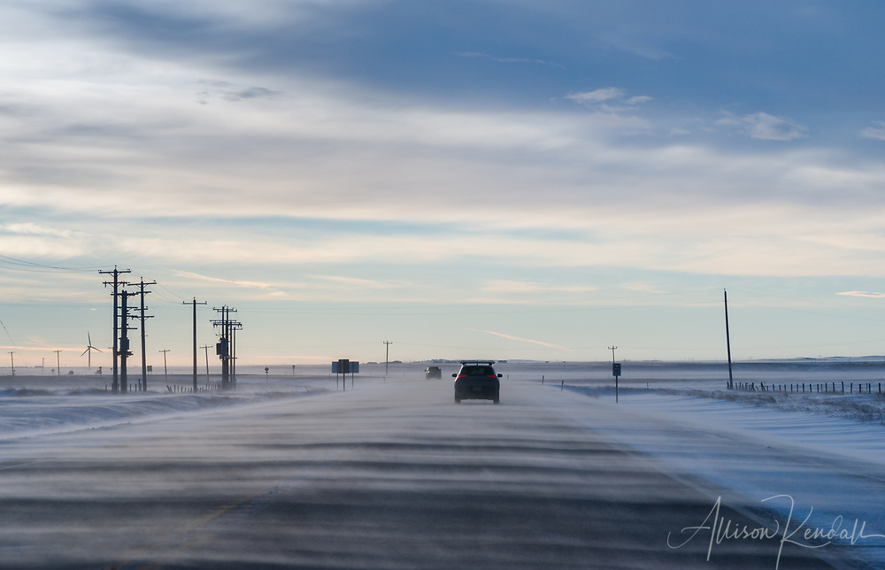 Snow blows across the landscape and Crowsnest Highway in Southern Alberta, Canada