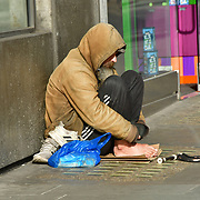 A beggar without mask begging at Oxford Street many shops closure a few open but empty on 21 March 2020, UK.