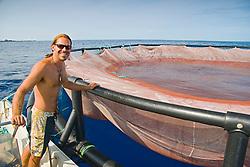 Kona Blue Fish Farms worker and one of the floating open ocean fish pens which is used to raise juvenile Kona Kampachi, Hawaiian yellowtail, aka almaco jack or kahala, Seriola rivoliana, off Kona Coast, Big Island, Hawaii, Pacific Ocean