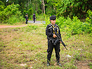 17 JUNE 2015 - RANGAE, NARATHIWAT, THAILAND:  Thai Army women Rangers on a defensive perimeter while members of their unit performed wellness checks during a mission in a Muslim village in Narathiwat. There are 5 platoons of women Rangers serving in Thailand's restive Deep South. They generally perform security missions at large public events and do public outreach missions, like home wellness checks and delivering food and medicine into rural communities. The medics frequently work in civilian clothes because the Rangers found people are more relaxed around them when they're in civilian clothes. About 6,000 people have been killed in sectarian violence in Thailand's three southern provinces of Narathiwat, Pattani and Yala since a Muslim insurgency started in 2004. Attacks usually spike during religious holidays. Insurgents are fighting for more autonomy from the central government in Bangkok.    PHOTO BY JACK KURTZ
