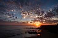 People line the cliffs to watch the sunset and surfers, West Cliff Drive, Santa Cruz, California