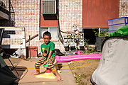 18 AUGUST 2020 - CEDAR RAPIDS, IOWA: A boy eats an ice cream novelty in front of Cedar Terrace Apartments in Cedar Rapids. Most of the tenants in the complex are refugees from Africa and Micronesia who have chosen the camp in front of the buildings rather than move to shelters because they're worried about looters taking their belongings. Cedar Rapids was the state's hardest hit city by the derecho that roared across Iowa last week. City officials said the damage left by the derecho was more extensive than the 2008 flood that destroyed much of its downtown. City residents are reporting that almost every home was damaged in the storm, many businesses were closed, and up to half of the city's tree canopy was destroyed. A week after the storm, more than 40,000 homes were still without power. A spokesman for Alliant Energy said the utility has replaced as many power poles in one week that they normally replace in 8 months. On Monday, President Trump approved a $4 billion emergency declaration for Iowa to aid in derecho recovery.    PHOTO BY JACK KURTZ