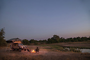 Tourists by camp fire and safari 4x4 in South Luangwa National Park, Zambia
