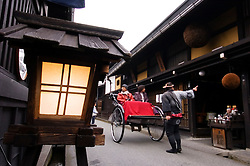 Tourists on rickshaw tour of historic Takayama in Japan