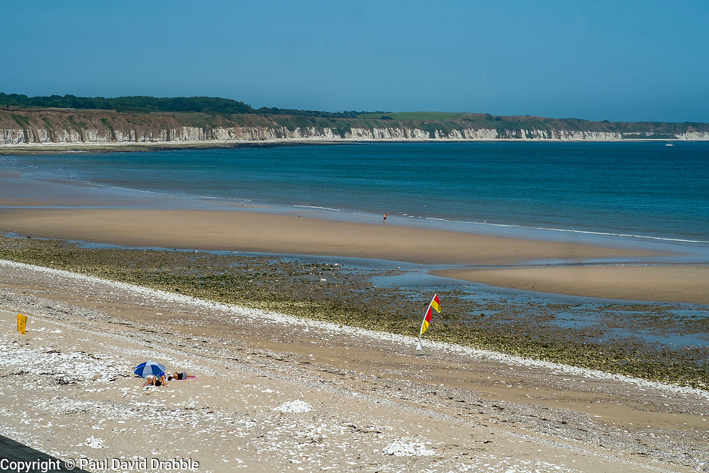 Holiday makers sit close to RNLI Life guards flags on Bridlington North Beach with their own blue and white sun shade<br /> <br />   05 July 2018 <br />   Copyright Paul David Drabble<br />   www.pauldaviddrabble.co.uk