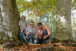 Father showing something to his sons in forest, Bavaria, Germany
