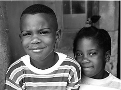 Young brother and sister standing close together,