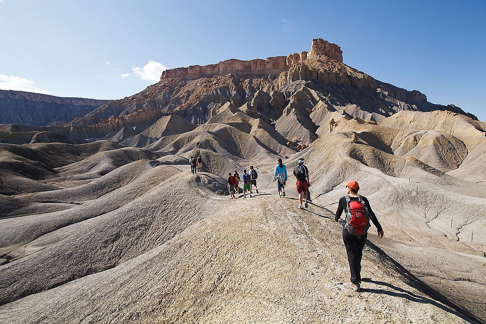 A group of students from the University of Colorado course in geomorphology hike into the mancos shale badlands on BLM land near Factory Butte, Utah.
