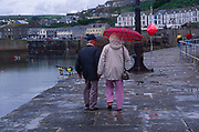 AE2MG9 Elderly couple walking away from camera in wet weather with umbrella Porthleven Cornwall England