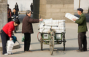Women buy toilet paper from tradesman from carts in street market by the City Wall, Xian, China