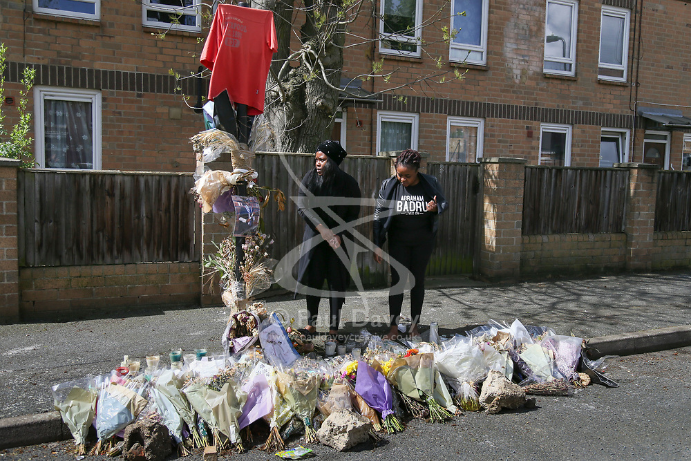 Two family members lay flowers at the spot where Abraham Badru was shot. Abraham Badru, a personal trainer, 26, was shot in the chest on 25th March in Ferncliff Road, E8. He received a National Police Bravery Award after intervening in a rape and giving evidence in court. London, April 25 2018.