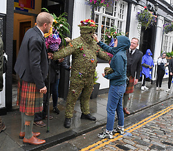 Pictured: Burryman Andrew Taylor get's some last minute repairs before he sets off on his tour of the town with his attendants and followers.<br /> <br /> The folklore character the Burryman carried out his annual walk through the streets of Queensferry to mark the start of the Ferry Fair, traditionally having a glass of whisky at every bar on the route. Covered head to toe in over 20,000 burrs, the tradition dates back hundreds of years.<br /> <br /> © Dave Johnston / EEm