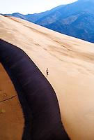 Woman running, Great Sand Dunes National Park, near Alamosa, Colorado USA