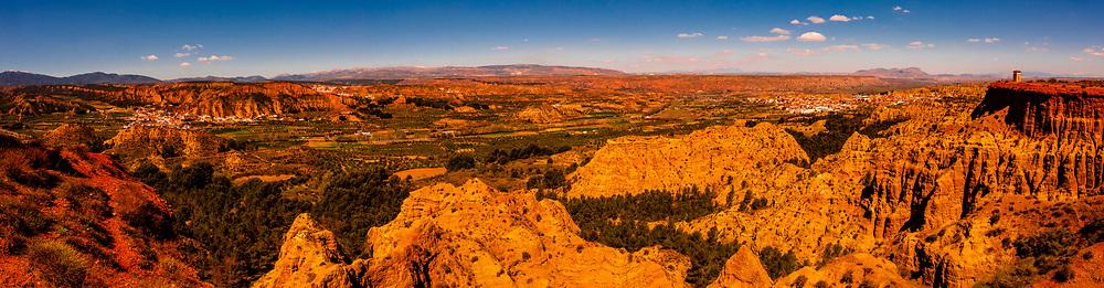 anoramic view of Badlands from Mirador del Fin del Mundo (the towns of Purullena-far left, Los Banos-above, center and Purullena-far right), near Guadix, Granada Province, Andalusia, Spain.