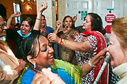 Elderly ladies dancing during a multi faith party at the Neighbourly Care day centre in Southall.