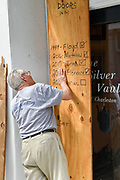 Charleston, South Carolina, USA. 03 September 2019. A shopkeeper attachs a plywood board listing all the previous hurricanes the store has weathered in preparation for Hurricane Dorian on historic King Street September 3, 2019 in Charleston, South Carolina. The slow moving monster storm devastated the Bahamas and is expected to reach Charleston as a Category 2 by Thursday morning.